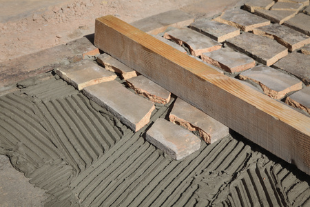 Old tiles recycling, making terrace or pavement using tile pieces, mortar and tile adhesive Stock Photo