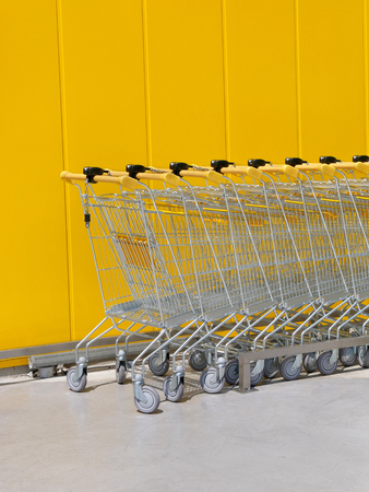 Stack of new shiny shopping carts in a supermarket with yellow wall in background