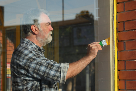 Adult man paint metal window to yellow color, old shop window renovation Stockfoto