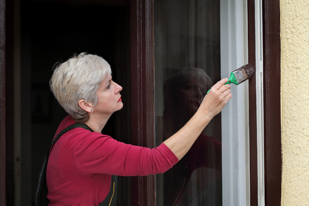 Adult female worker paint wooden window to brown color, old house window renovation Standard-Bild - 114955771