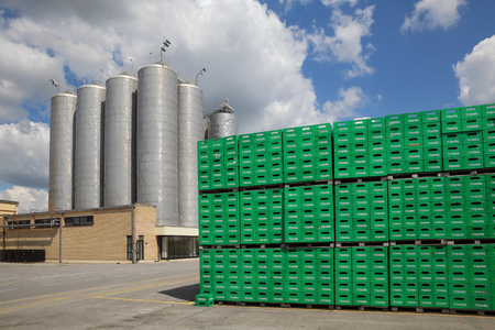 CELAREVO, SERBIA - JUNE 11. 2017. Carlsberg Serbia brewery, heap of green crates for Tuborg beer  at large warehouse with storage tanks and factory in background Sajtókép