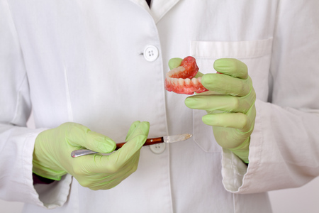 Dentist modeling wax prothesis model using dental modeling knife, closeup of hands in gloves and tool