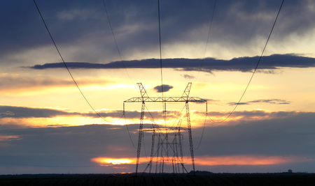 High voltage electricity power lines and pylons in sunset with beautiful sky