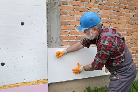 Worker placing  polystyrene  insulation to brick wall, house renovation