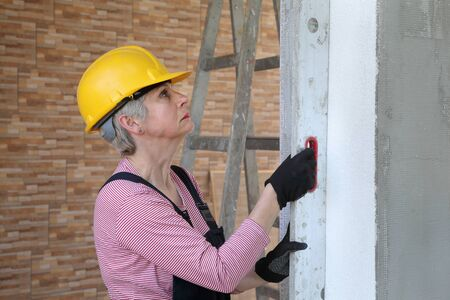 Female worker control  polystyrene insulation of wall with level tool Stock fotó