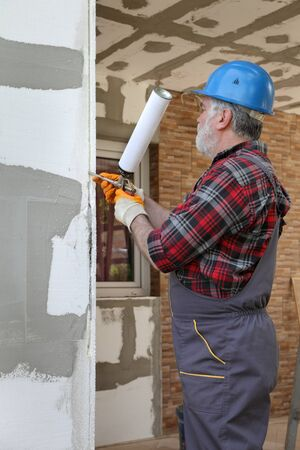 Worker applying adhesive glue to wall, polystyrene insulation of wall using applicator gun