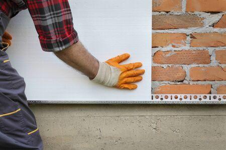 Trabajador colocando espuma, aislamiento térmico de poliestireno a la pared de ladrillo, renovación de la casa Foto de archivo