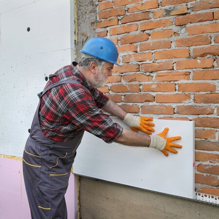 Worker placing foam, polystyrene thermal insulation to brick wall, house renovation