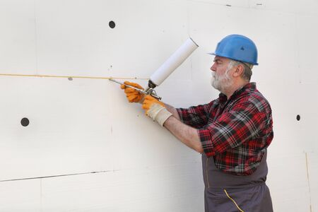 Worker applying adhesive glue to foam, polystyrene thermal insulation of wall using applicator gun Stock fotó