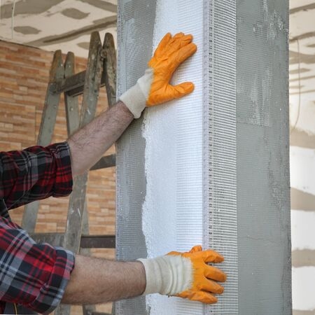 Worker placing reinforcing corner mesh to pillar over foam insulation
