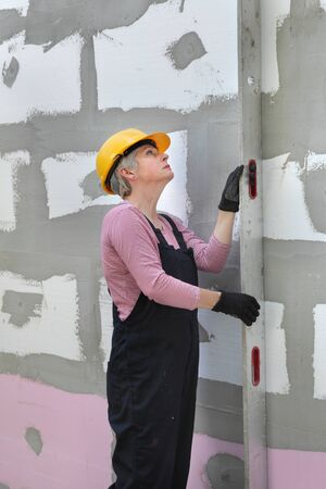 Female worker control foam, polystyrene insulation of wall with level tool Stock fotó