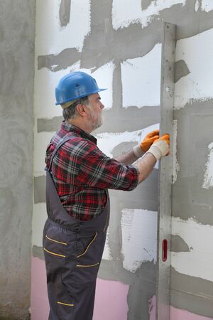 Worker control foam, polystyrene insulation of wall with level tool Stock fotó
