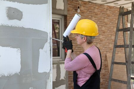 Female worker applying adhesive glue to foam, polystyrene insulation of wall using applicator gun Stock fotó