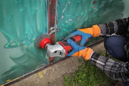 Paint and rust removing from metal plate, worker using wire brush at grinder power tool Stock fotó
