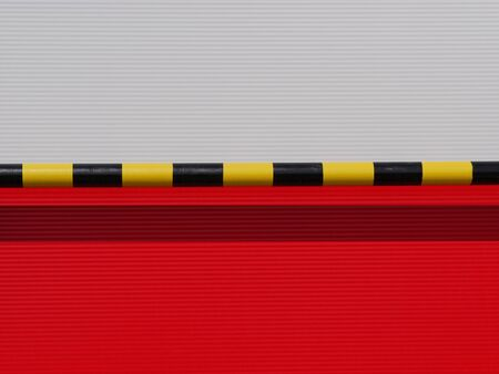 New red and white metal panel construction with car stopper barrier, wall of industrial building