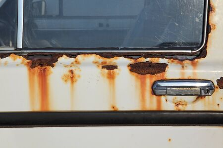 Detail of old rust white car, closeup of corrosion at metal
