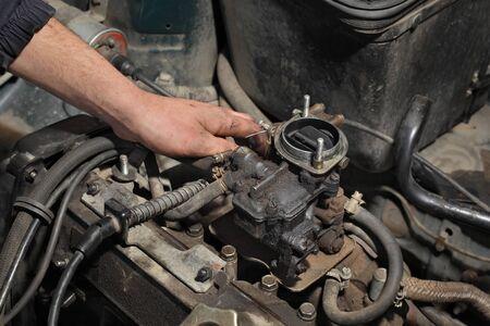 Car mechanic fixing carburetor at old greasy gasoline engine