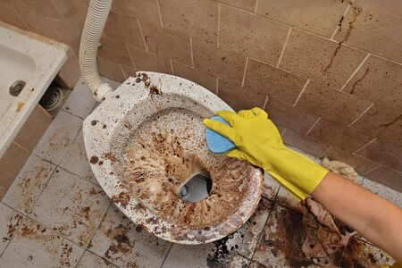 Female hand in protective glove cleaning dirty toilet using sponge, messy toilet in a dirty bathroom, very bad condition Stockfoto