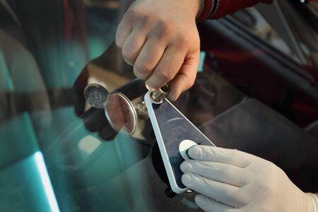 Mechanic using repairing equipment to fix damaged windshield Stockfoto