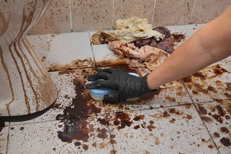 Female hand in protective glove cleaning dirty toilet, tiles using sponge, messy toilet in a dirty bathroom, very bad condition