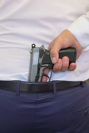 Human hand holding gun behind belt in pants in the back of a man