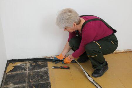 Female worker removing old batten and vinyl tiles from kitchen floor
