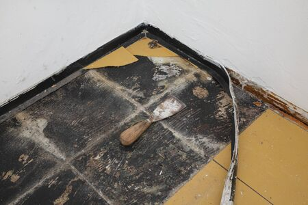 Old vinyl tiles and batten removing from kitchen floor, spatula trowel Imagens