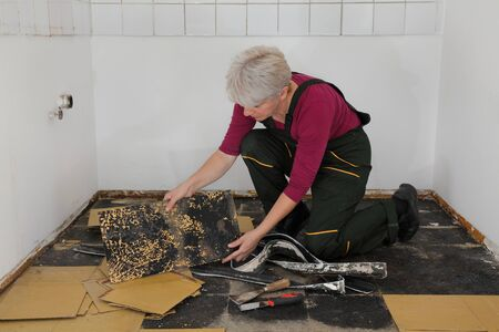 Female worker removing old vinyl tiles from kitchen floor using spatula trowel tool