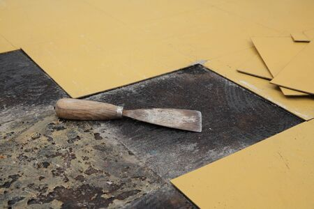 Old vinyl tiles removing from kitchen floor, closeup of spatula trowel, selective focus