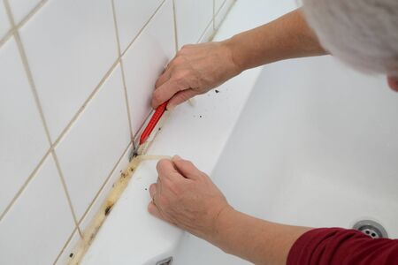 Plumber removing old dirty silicone from bathtube in a washroom, cutting of silicone glue using cutter