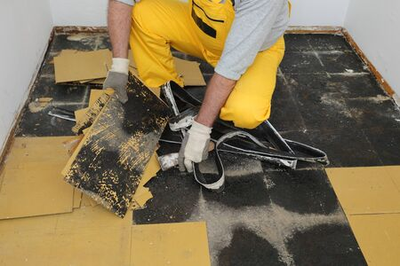 Worker removing old vinyl tiles from kitchen floor using spatula trowel tool
