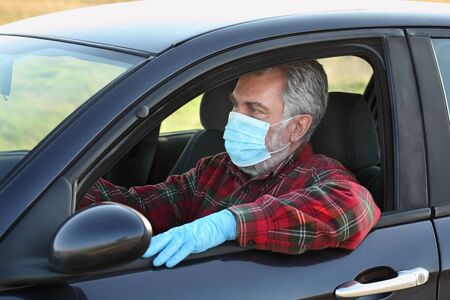 Adult driver with protective surgical mask and gloves sitting in a car, corona virus protected person