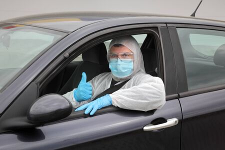 Adult driver with protective cloth, surgical mask, glasses and gloves gesturing with thumb up from car, corona virus protected person