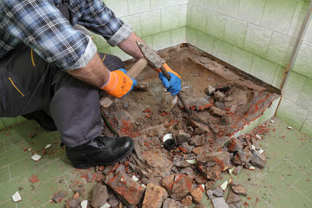 Worker remove, demolish old bathtub and tiles with hammer and chisel in a bathroom