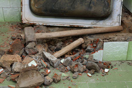 Home renovation, old bathtub and tiles demolishing in bathroom, hammer tool