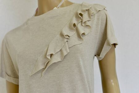 Womens knitted T-shirt with frill. Color gently sandy beige powdery. Fragment Close-up. For shops.