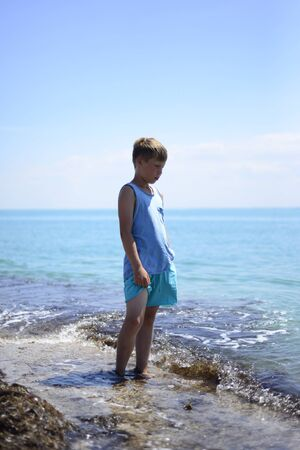 A boy stands in shallow water at sea. Hes sad. He looks at the turquoise water and thinks. Free space for text.