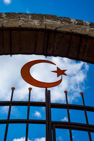 Muslim symbol half moon and star on a background of sky and clouds. Arch and fence grille. Imagens