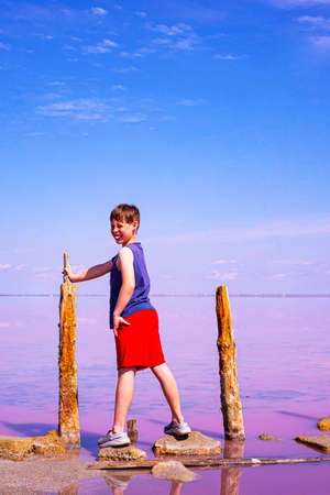 The boy is smiling. Good mood. He has a white-toothed smile. A boy in red shorts on a background of blue sky and pink lake. Copy space for text.