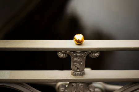 Metallic gray railing with a golden decorative ball on the background of the river.