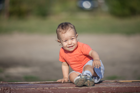 brown  eyed: Dirty with sand little boy sits on a bench in a park. Stock Photo