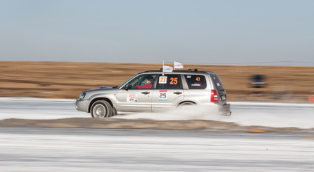 forester: Moscow, Russia - March 1st, 2014: Moscow Subaru Forester club championship. This stage was located in Moscow, on the frozen pond track. The track was build by club members. Woman driving her silver Subaru Forester on ice track, car sliding on the ice, sno
