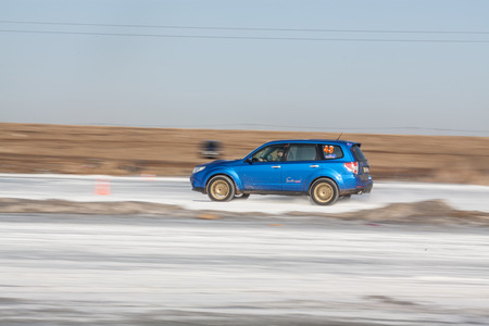 forester: Moscow, Russia - March 1st, 2014: Moscow Subaru Forester club championship. This stage was located in Moscow, on the frozen pond track. The track was build by club members. Man driving his blue subaru Forester TS on ice track, car sliding on the ice, snow
