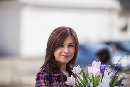 topcoat: Young woman portrait, smiling and holding tulips in her hands
