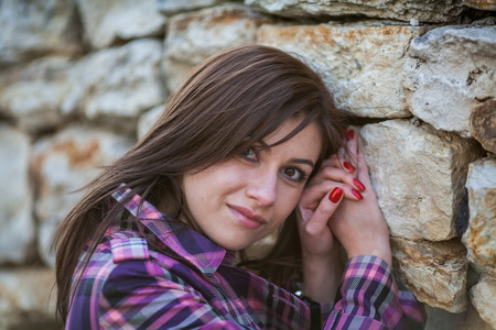 topcoat: Young woman in sunshine portrait, looks straight to you, near the  stone wall with big rocks Stock Photo