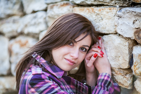 large rock: Young woman in sunshine portrait, looks straight to you, near the stone wall with big rocks