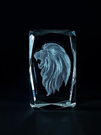 engraver: Laser engraving lion inside the glass on a black background.