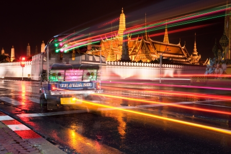 tuk tuk: A long time exposure of a tuk tuk passing in front of the Grand Palace district with the sacred Temple of the Emerald Buddha (Wat Phra Kaew) visible in the background.  The three-wheeled tuk tuks are a typical means of transportation in the Thai capital  Stock Photo