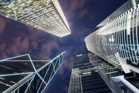 high rise buildings: A bottom up view of Hong Kong skyscrapers at night in the central business district on Hong Kong Island  Stock Photo