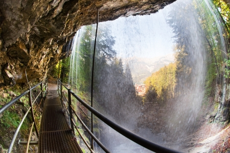 bernese oberland: Fisheye view of a footbridge leading behind the giessbach falls at lake Brienz in the Bernese Oberland, Switzerland - the historic Grand Hotel Giessbach is visible  through the waterfall  Stock Photo